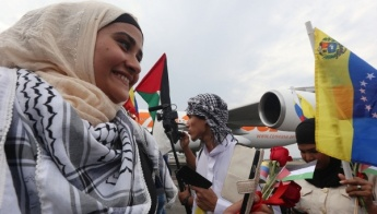A Palestinian woman is greeted by a crowd upon her arrival in Venezuela AVN
