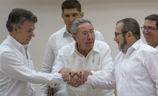 President Santos (left) and FARC's chief, Rodrigo Londoño (Timochenko) shook hands after a meeting facilitated by Raul Castro (centre)