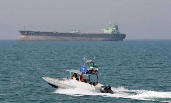 A tanker in the Strait of Hormuz. Foreground: Iranian naval vessel