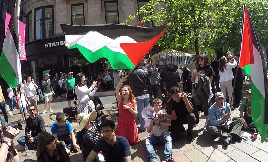 RCG and supporters hold a sit-down protest in front of a Glasgow Friends of Israel stall
