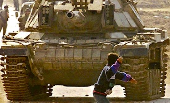 Boy throws stone at oncoming Israeli tank